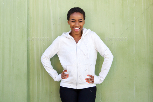 attractive young black woman laughing against green wall - Stock Photo - Images