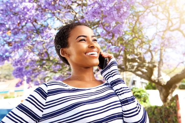 happy young woman smiling outside with cellphone - Stock Photo - Images