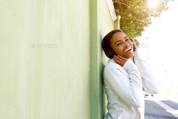 Young black woman enjoying listening to music with headphones - Stock Photo - Images
