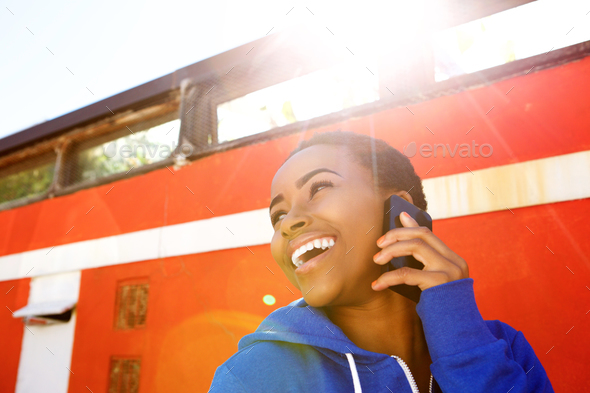 cool young black woman laughing with cellphone - Stock Photo - Images