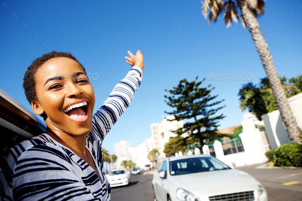 young woman hanging outside car window with arms raised - Stock Photo - Images