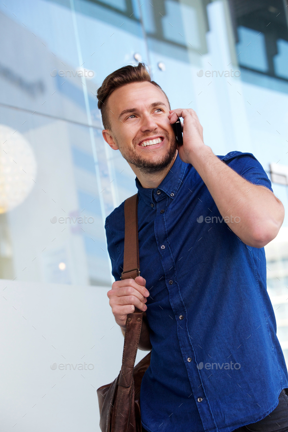 handsome young man walking with mobile phone - Stock Photo - Images