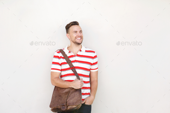 smiling young man standing against white wall with bag - Stock Photo - Images