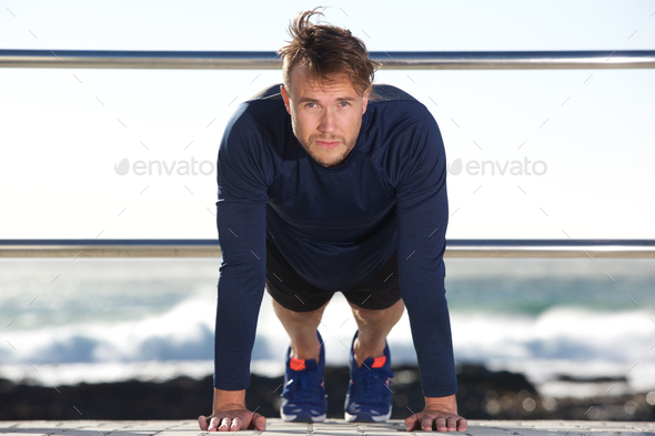 handsome young man doing push ups outdoors - Stock Photo - Images