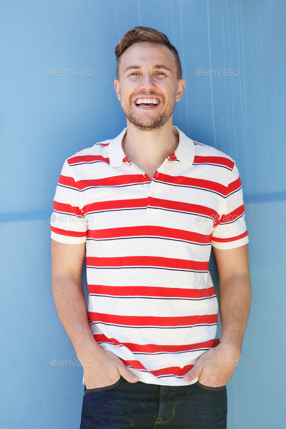 handsome young man in striped shirt laughing against blue wall - Stock Photo - Images