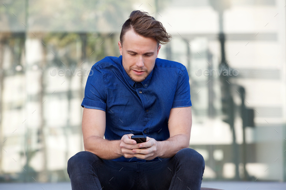 one guy sitting outside in city with mobile phone - Stock Photo - Images