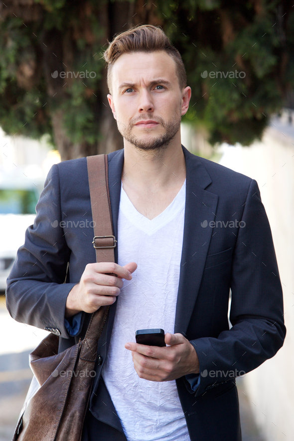 Young businessman walking outside with mobile phone and bag - Stock Photo - Images