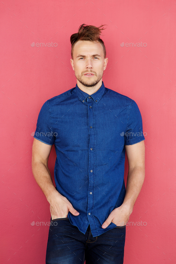 cool fashion model with blue shirt standing against red wall - Stock Photo - Images