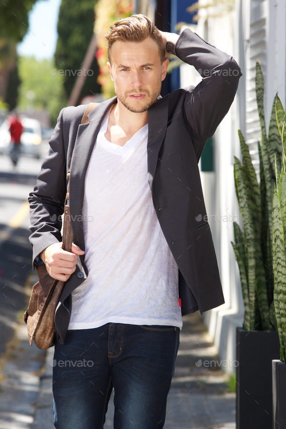 male fashion model with bag walking outside - Stock Photo - Images