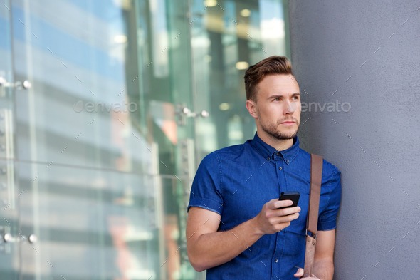 handsome young man leaning against wall outside with cellphone - Stock Photo - Images