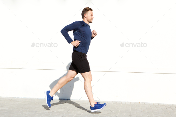 happy man running outside against white wall - Stock Photo - Images