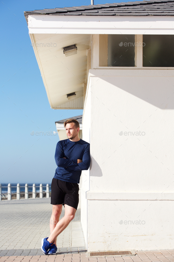 confident young sports man leaning on wall outside - Stock Photo - Images