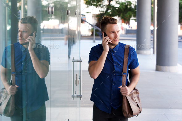 cool fashion guy walking with cellphone and bag - Stock Photo - Images