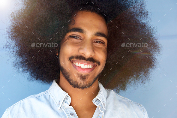 smiling man with afro and beard by blue wall - Stock Photo - Images