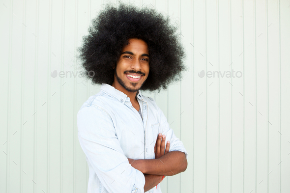 happy man with beard and afro standing with arms crossed - Stock Photo - Images