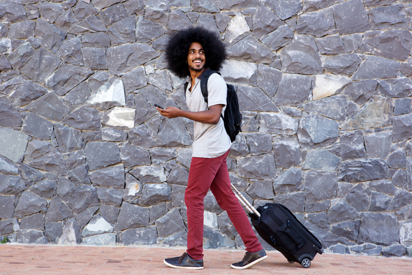 smiling travel man with phone and bags walking outside - Stock Photo - Images