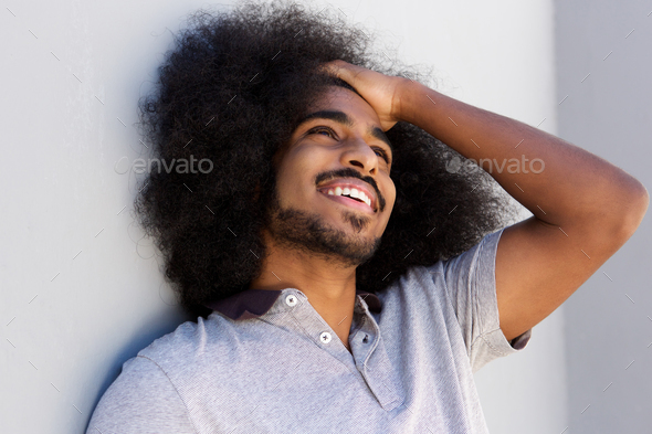 laughing afro man with hand in hair looking away - Stock Photo - Images