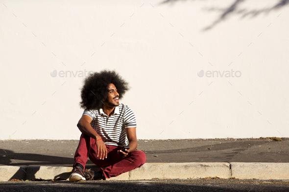 happy man sitting on sidewalk outside with phone - Stock Photo - Images