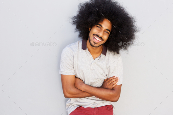 smiling man with afro standing with arms crossed - Stock Photo - Images