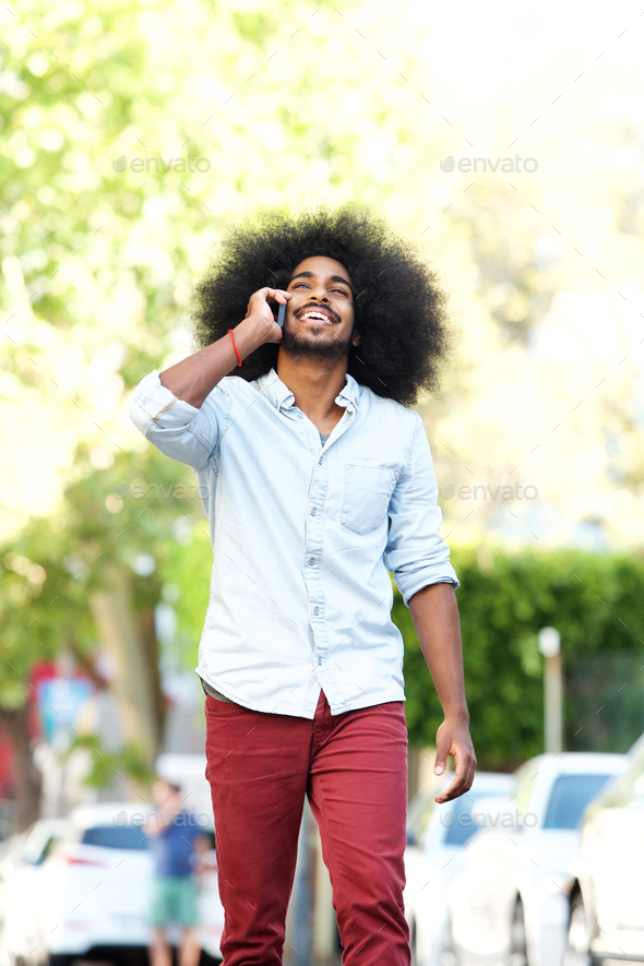 happy man walking and talking outside with mobile phone - Stock Photo - Images