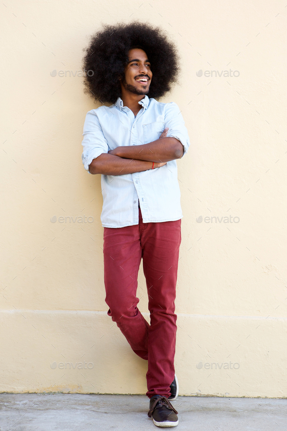 young afro man with afro smiling standing with arms crossed - Stock Photo - Images