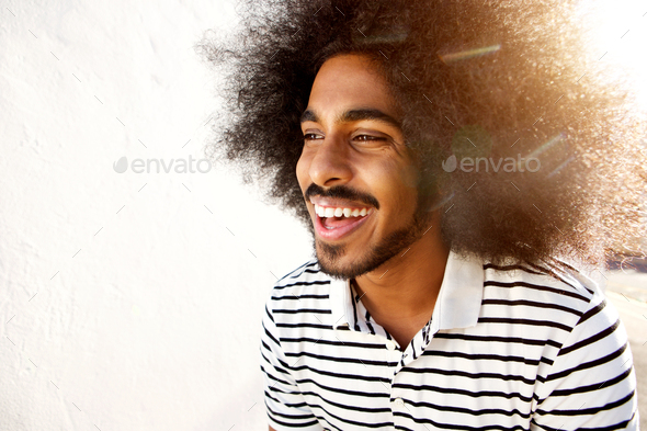 laughing afro man in sunlight - Stock Photo - Images