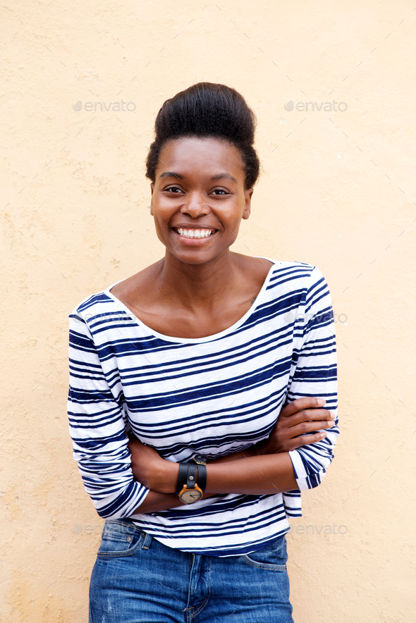 smiling young african woman with arms crossed - Stock Photo - Images
