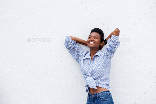 cheerful black woman smiling with hands behind head - Stock Photo - Images