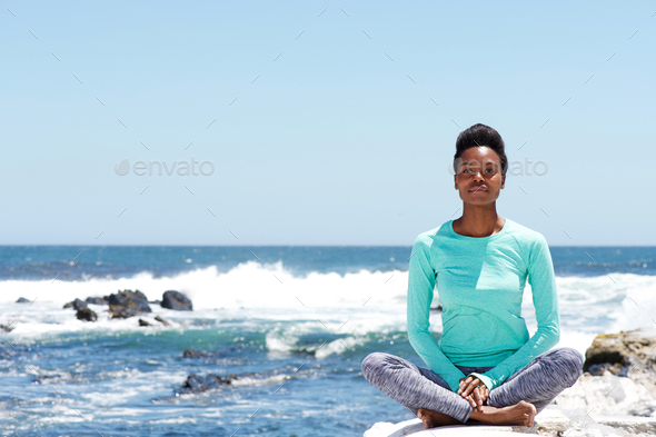 young african american woman doing yoga at the beach - Stock Photo - Images