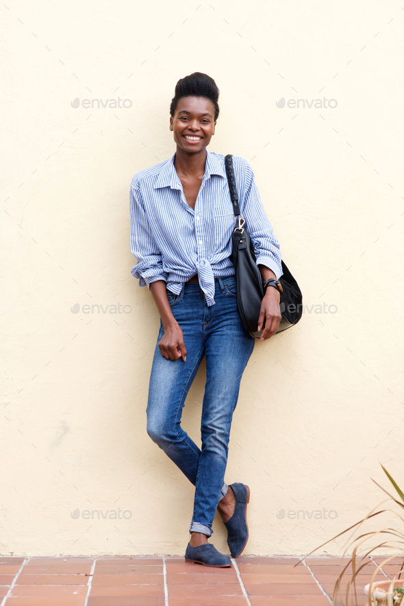 smiling black woman leaning against wall - Stock Photo - Images