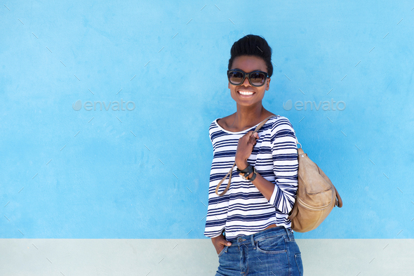 cool young woman smiling with handbag - Stock Photo - Images