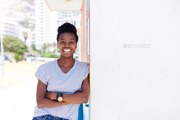confident young woman smiling against shite wall - Stock Photo - Images