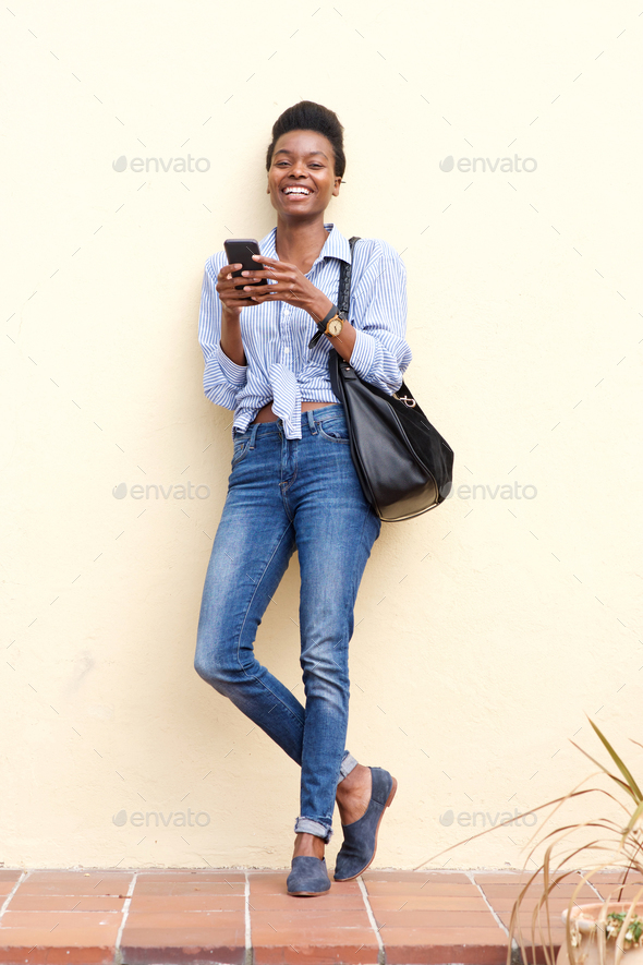 smiling black woman using mobile phone - Stock Photo - Images