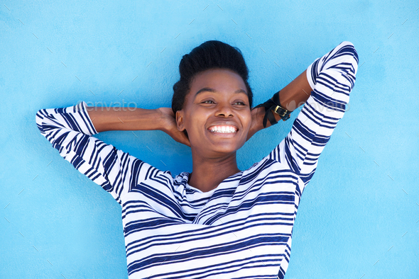 smiling young black woman with hands behind head - Stock Photo - Images