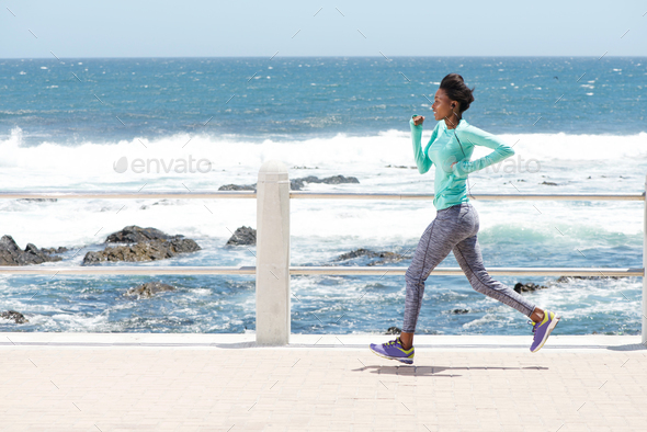 young african american woman running by the sea - Stock Photo - Images