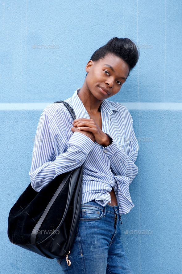 african american woman leaning against wall with handbag - Stock Photo - Images