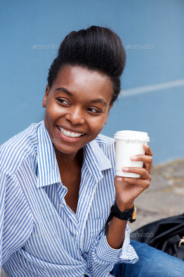 beautiful young black woman smiling with cup of coffee - Stock Photo - Images