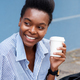 beautiful young black woman smiling with cup of coffee - PhotoDune Item for Sale