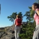Two Active Young Women Help Each Other To Climb a High Rock - VideoHive Item for Sale