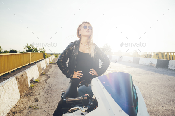 Biker woman looking interested to the sky - Stock Photo - Images