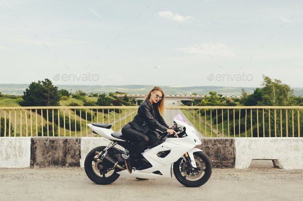 Beautiful woman with sunglasses driving on motorbike - Stock Photo - Images