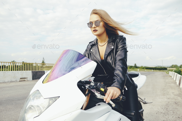 Fashionable woman driving a bike on a road - Stock Photo - Images