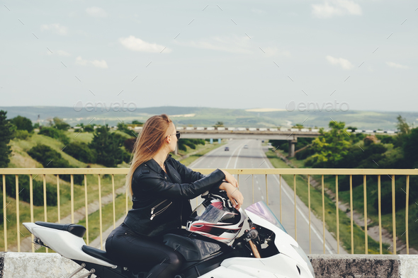 Young woman thinking of new destinations while sitting on bike - Stock Photo - Images