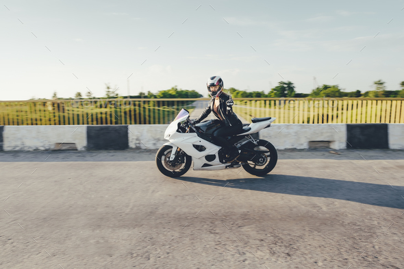Woman biker driving a motorbike on a road - Stock Photo - Images