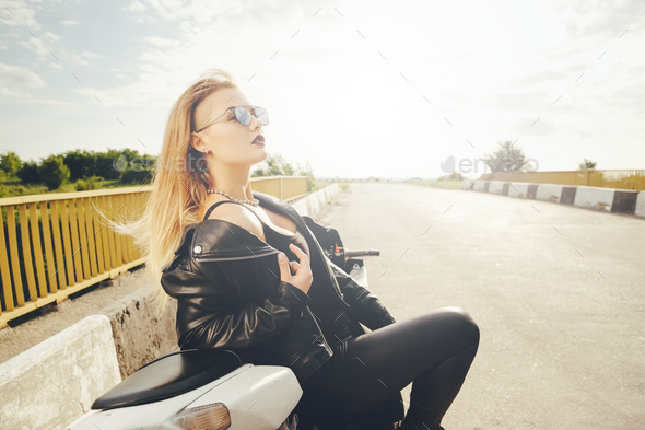 Beautiful woman posing with sunglasses on a motorbike - Stock Photo - Images