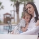 Mother and Sad Daughter Sitting at a Table By the Pool - VideoHive Item for Sale