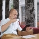 Young Man with Tablet Computer Drinking Coffee in Cafe - VideoHive Item for Sale