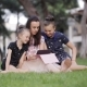 Mother and Daughter on the Grass with Tablet. Mom Reads a Story To Two Daughters in the Meadow - VideoHive Item for Sale