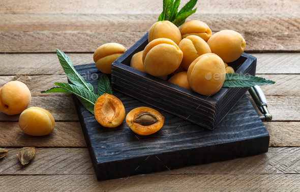 Delicious ripe apricots in a wooden box on the table close-up. - Stock Photo - Images
