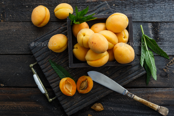 Delicious ripe apricots in a wooden box on dark wooden background, rustic style - Stock Photo - Images